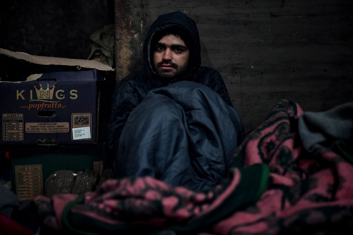 Mohamed Darwich,a 17-year old migrant from Afghanistan, poses in a makeshift shelter at an abandoned warehouse in Belgrade on December 8, 2016.