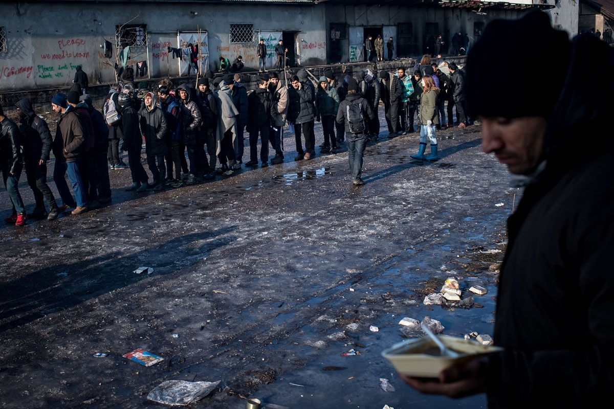 Migrants stand in line for food distributed by volunteers outside of derelict warehouses which they use as a makeshift shelter, in Belgrade on January 15, 2017, with temperatures just bellow zero Celsius overnight.