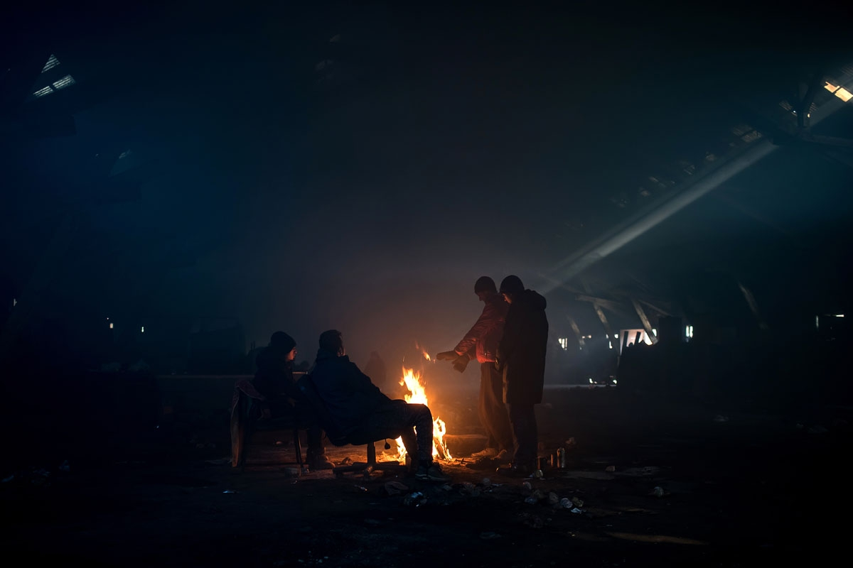 Migrants warm up around a fire inside a derelict warehouse used as a makeshift shelter in Belgrade on January 15, 2017, with temperatures just bellow zero Celsius overnight.