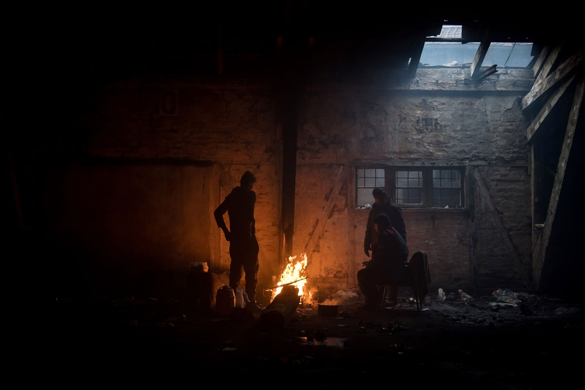 Migrants gather around a bonfire inside of derelict warehouse used as a shelter near Belgrade's main railway station on January 17, 2017, with temperatures bellow zero Celsius.