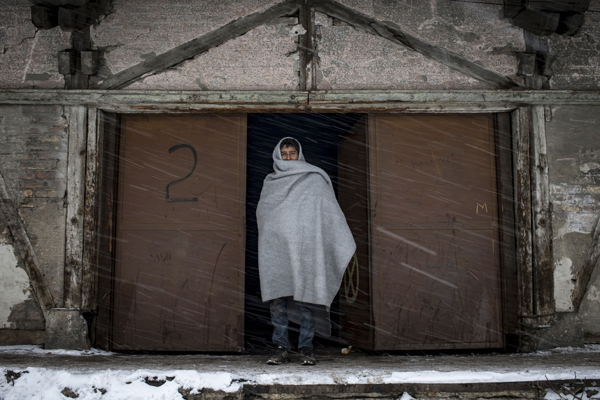 A migrant walks out of a makeshift shelter at an abandoned warehouse in Belgrade on January 11, 2017, as temperatures dropped to -15 degrees Celsius overnight.
