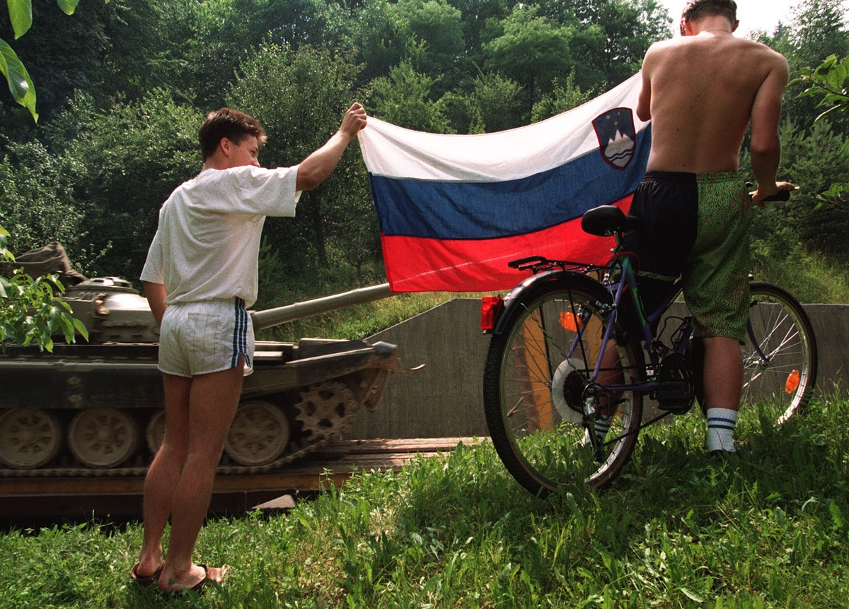 Two Slovenian youths hold up the flag of their breakaway republic as a Yugoslavian army T