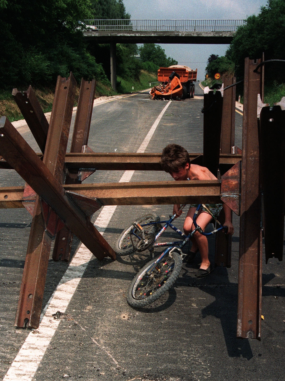 A Slovenian child bends down to slide his bicycle under anti tank barricades on the road