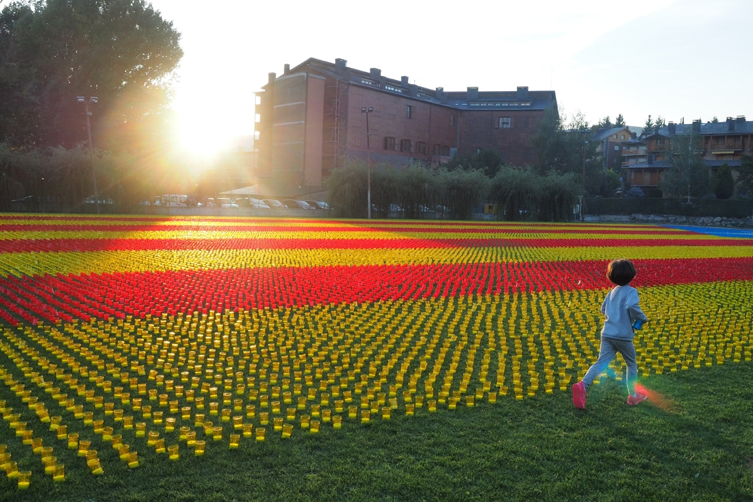 A child runs by a Catalonia's independantist flag made of 82000 candles in Llivia, in the Spanish Pyrenees near the French and Andorran borders on September 23, 2017