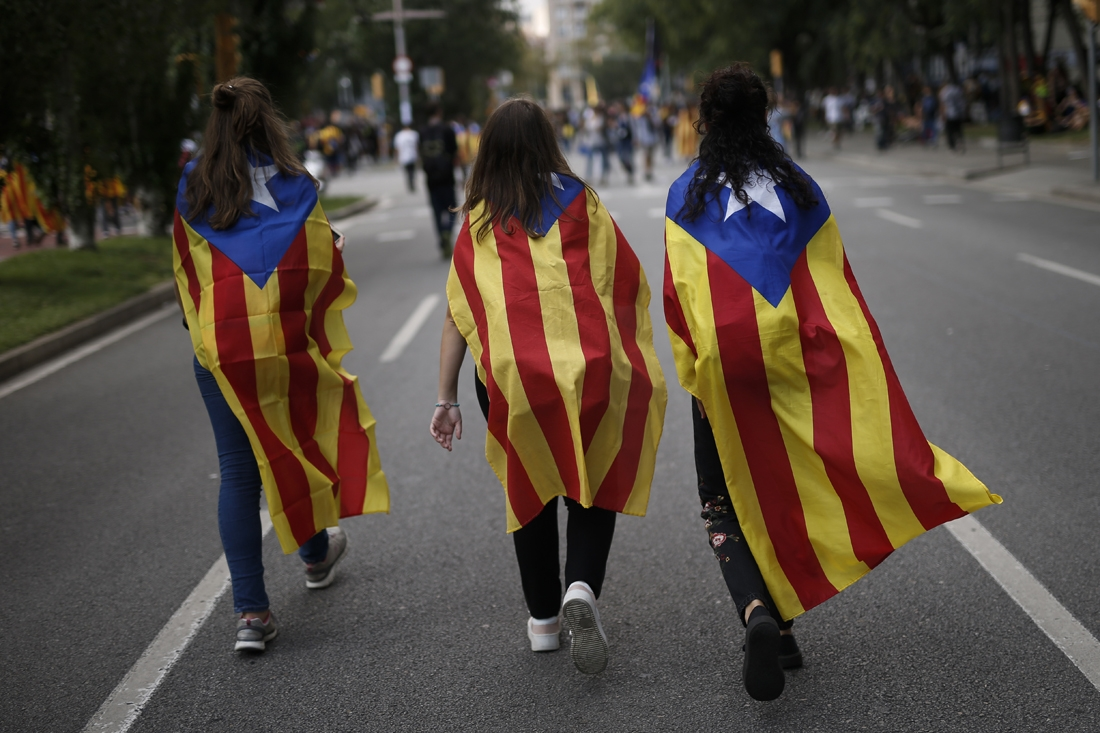 Three girls walk as they sport Esteladas (Pro-independence Catalan flags) during a pro-referendum demonstration on September 28, 2017 in Barcelona.