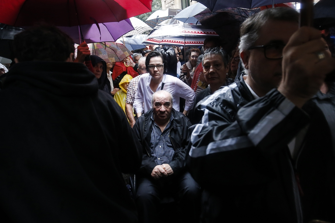 People wait under the rain outside the Concepcio School in Barcelona on October 1, 2017 to vote in a referendum on independence for Catalonia banned by Madrid. /