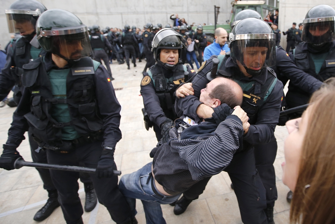 Spanish Guardia Civil guards drag a man outside a polling station in Sant Julia de Ramis, where Catalan president was supposed to vote, on October 1, 2017, on the day of a referendum on independence for Catalonia banned by Madrid.