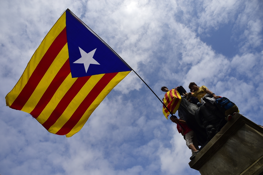 Protesters wave a giant Catalan pro-independence 'Estelada' flag atop a sculpture during a demonstration in Barcelona on October 2, 2017 a day after hundreds were injured in a police crackdown during Catalonia's banned independence referendum.