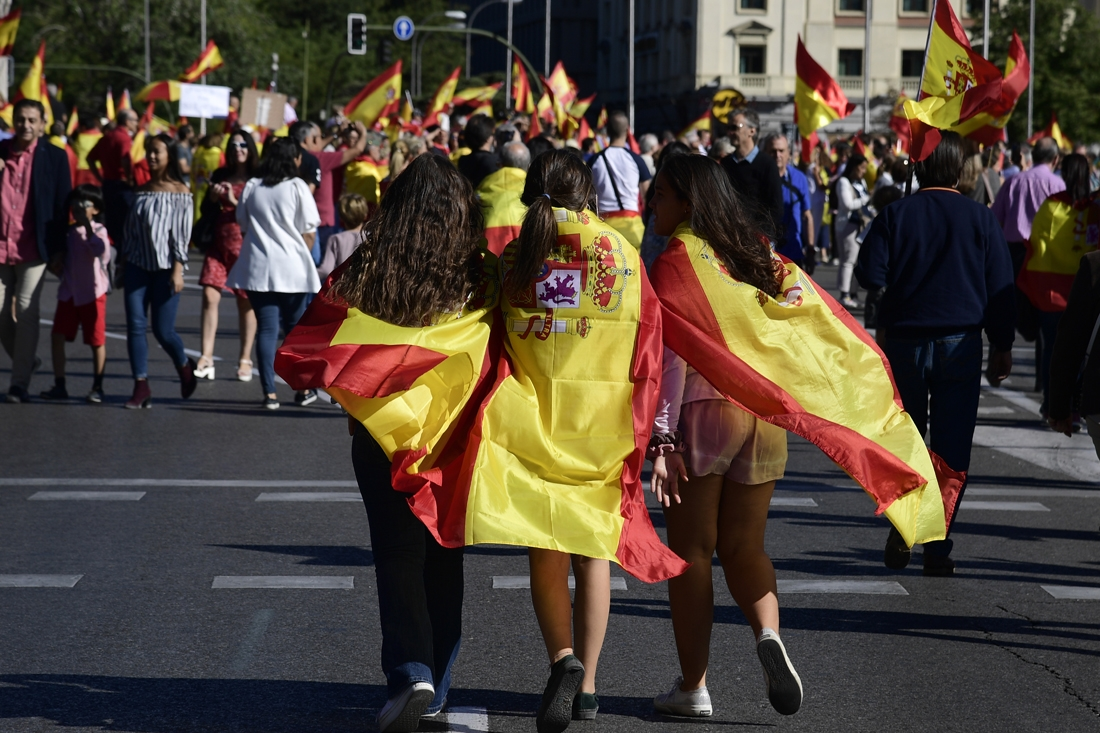 Young girls wrapped in Spanish flags gather during a demonstration against independence of Catalonia called by DENAES foundation for the Spanish Nation Defence at Colon square in Madrid on October 07, 2017.