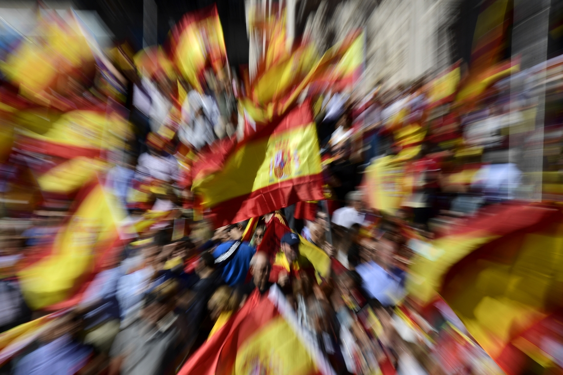 Protestors gather holding Spanish flags during a demonstration against independence of Catalonia called by DENAES foundation for the Spanish Nation Defence at Colon square in Madrid on October 07, 2017.