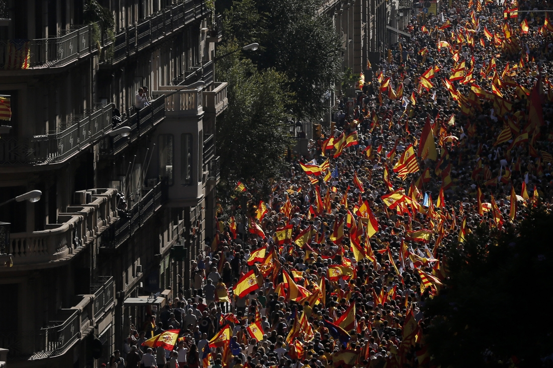 Protesters hold Spanish flags during a demonstration called by Societat Civil Catalana (Catalan Civil Society) to support the unity of Spain on October 8, 2017 in Barcelona.
