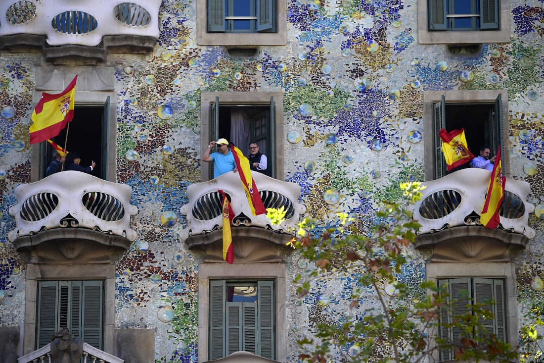 People wave Spanish flags from the Casa Batllo during a pro-unity demonstration in Barcelona on October 29, 2017. Pro-unity protesters were to gather in Catalonia's capital Barcelona, two days after lawmakers voted to split the wealthy re