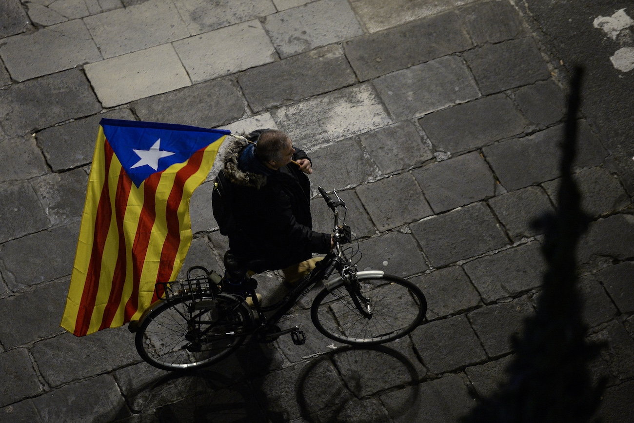 A man rides a bicycle holding a Catalan pro-independence 'Estelada' flag after a demonstration called by employees of the Generalitat (Government of Catalonia) at the Sant Jaume square in Barcelona on November 21, 2017 i