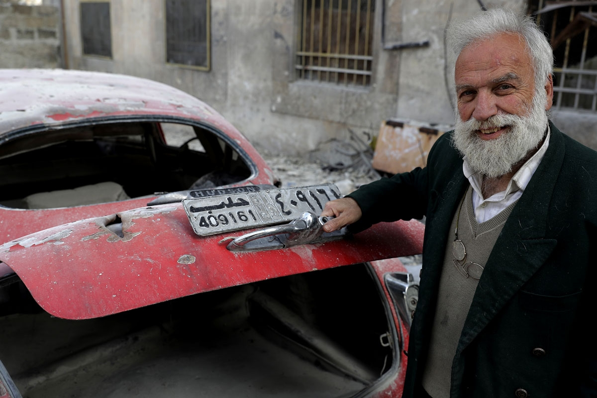 A picture taken on March 9, 2017, shows 70-year-old  opening the trunk of his 1949 Hudson Commodor outside his home in Aleppo's formerly rebel-held al-Shaar neighbourhood.