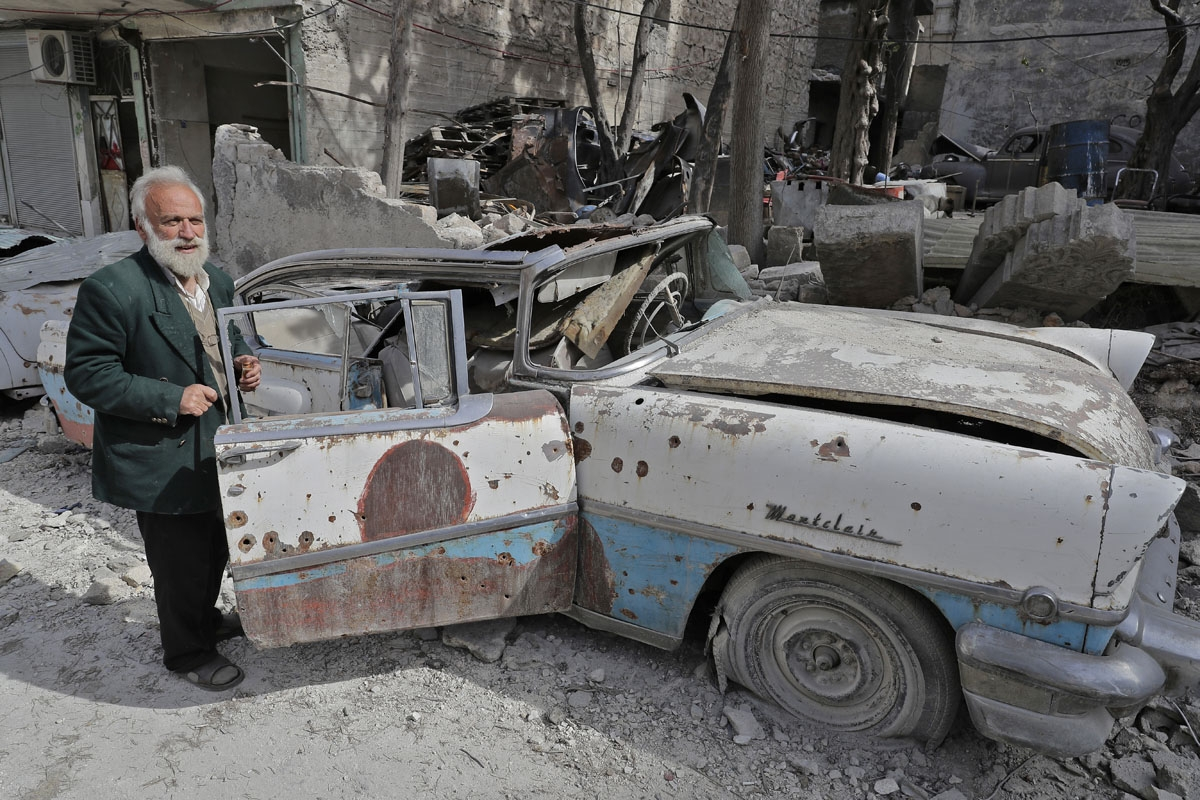 A picture taken on March 9, 2017, shows 70-year-old Mohammad Mohiedine Anis inspecting his 1957 Mercury Montclair outside his home in Aleppo's formerly rebel-held al-Shaar neighbourhood.