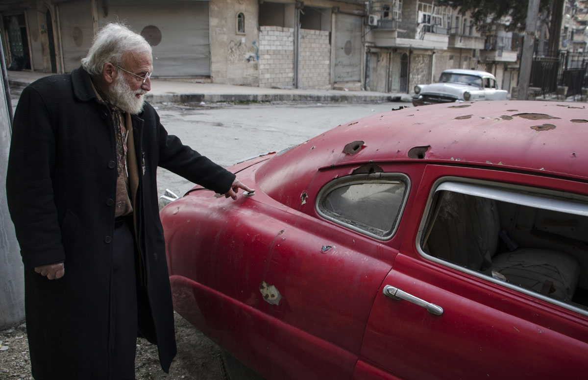 Abu Omar a 69-year-old Syrian classic car collector, gestures towards bullet holes on one of his cars in the rebel held al-Shaar district of the northern Syrian city of Aleppo, on December 20, 2015.