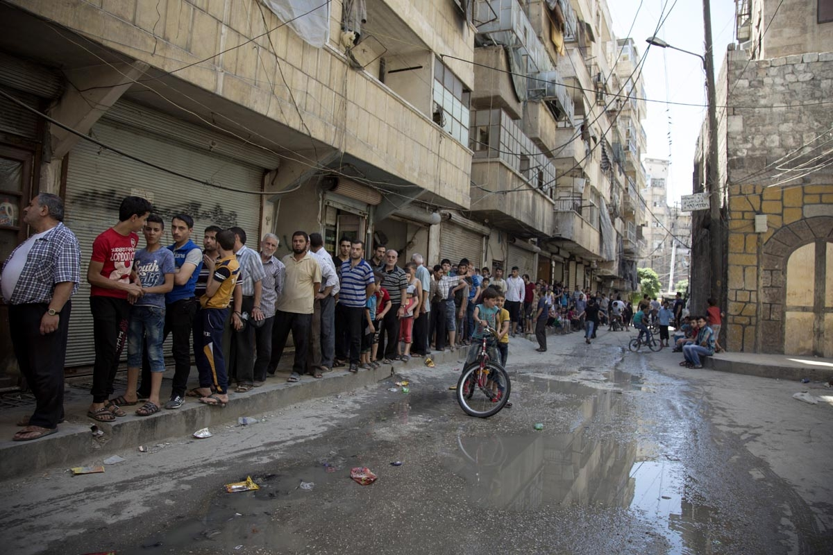 Syrians queue up to buy bread in a rebel held neighbourhood in the northern city of Aleppo on July 12, 2016.