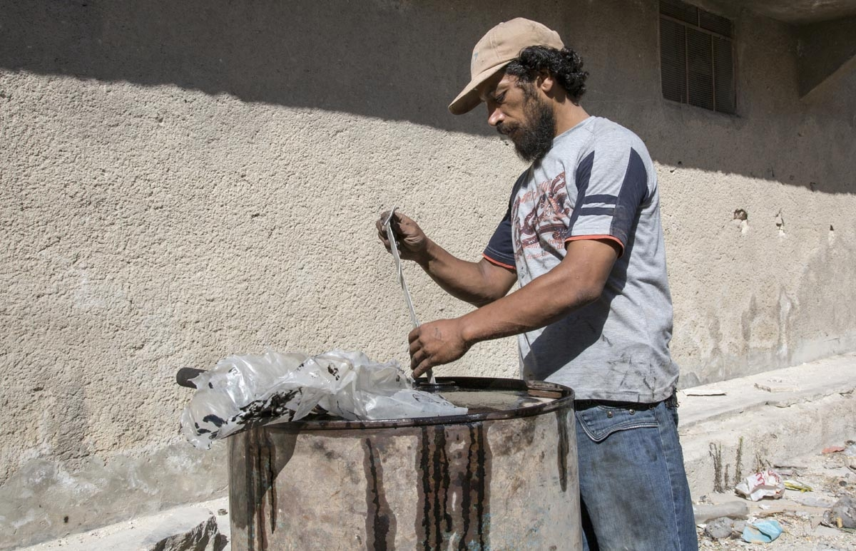 Abu Ahmed, a 40-year-old Syrian man, fills a barrel with plastic as part of a refining process to produce fuel on September 10, 2016, in Aleppo's rebel-held eastern district of Sakhur.