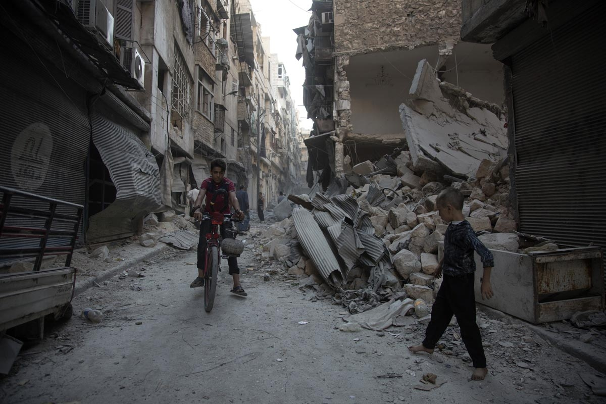 Syrians walk through the rubble following an air strike in Aleppo's rebel-controlled neighbourhood of Karm al-Jabal on September 18, 2016.