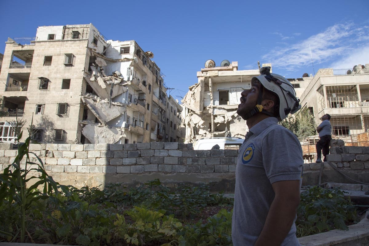 A Syrian rescuer looks towards the sky following an air strike in the rebel-held Ansari district in the northern Syrian city of Aleppo on September 23, 2016