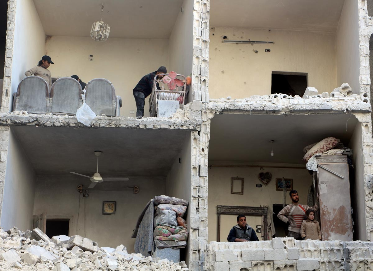 Civilians photographed in a damaged building in Syria's northern city of Aleppo following a reported air strike by government forces on December 7, 2015.
