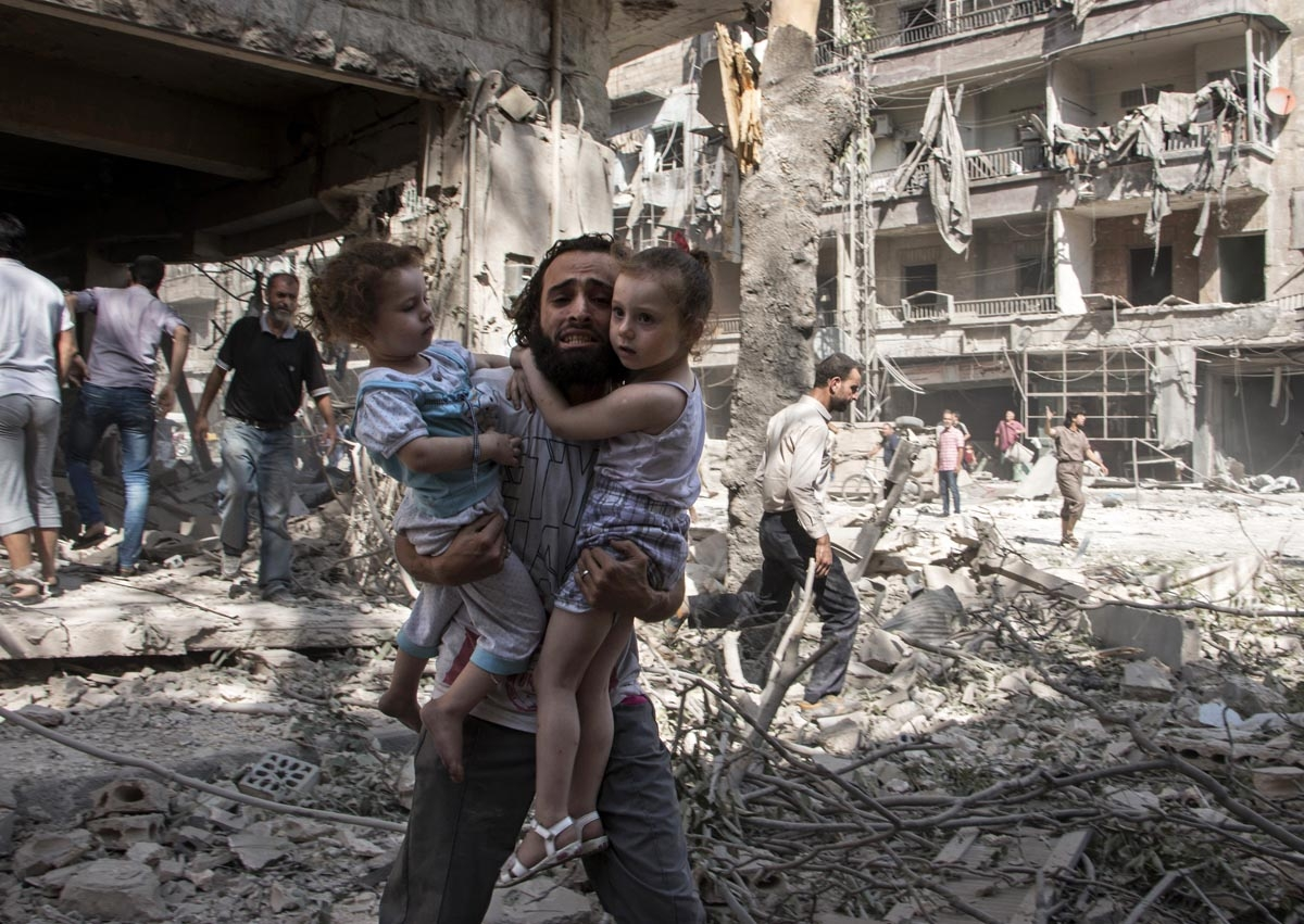A Syrian man carries his two girls as he walks across the rubble following a barrel bomb attack on the rebel-held neighbourhood of al-Kalasa in the northern Syrian city of Aleppo on September 17, 2015