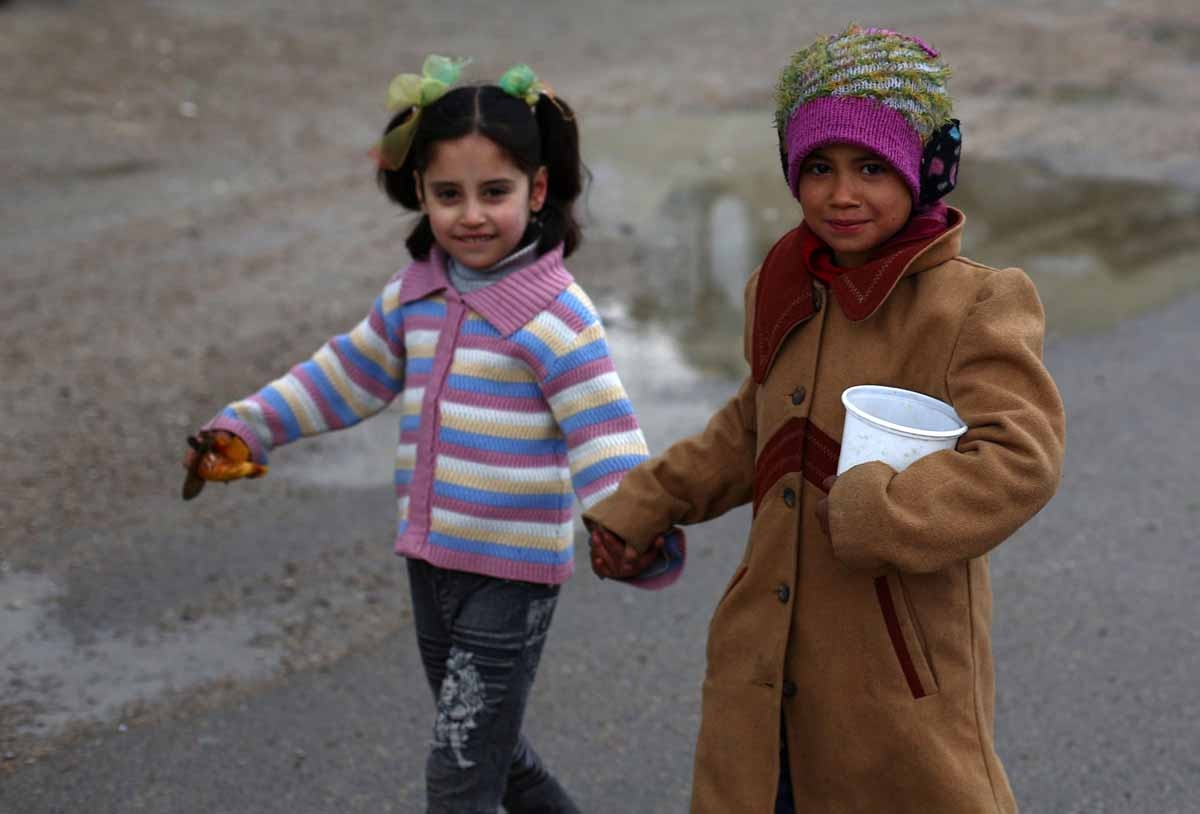 Young Syrian girls walk in a street on March 21, 2015 in the rebel-held area of Douma, east of the capital Damascus.