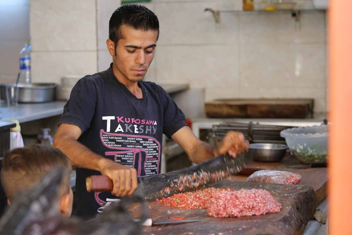 A Syrian man prepares food at a shop in the Kurdish-majority northeastern city of Qamishli on September 16, 2016.