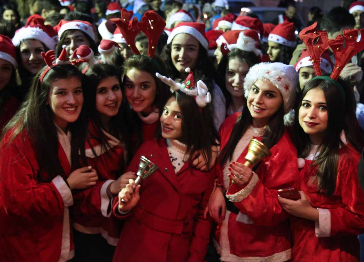 Syrian women dressed in Santa Claus outfits pose for a picture during Christmas celebrations in the northeastern Syrian city of Qamishli on December 24, 2015.