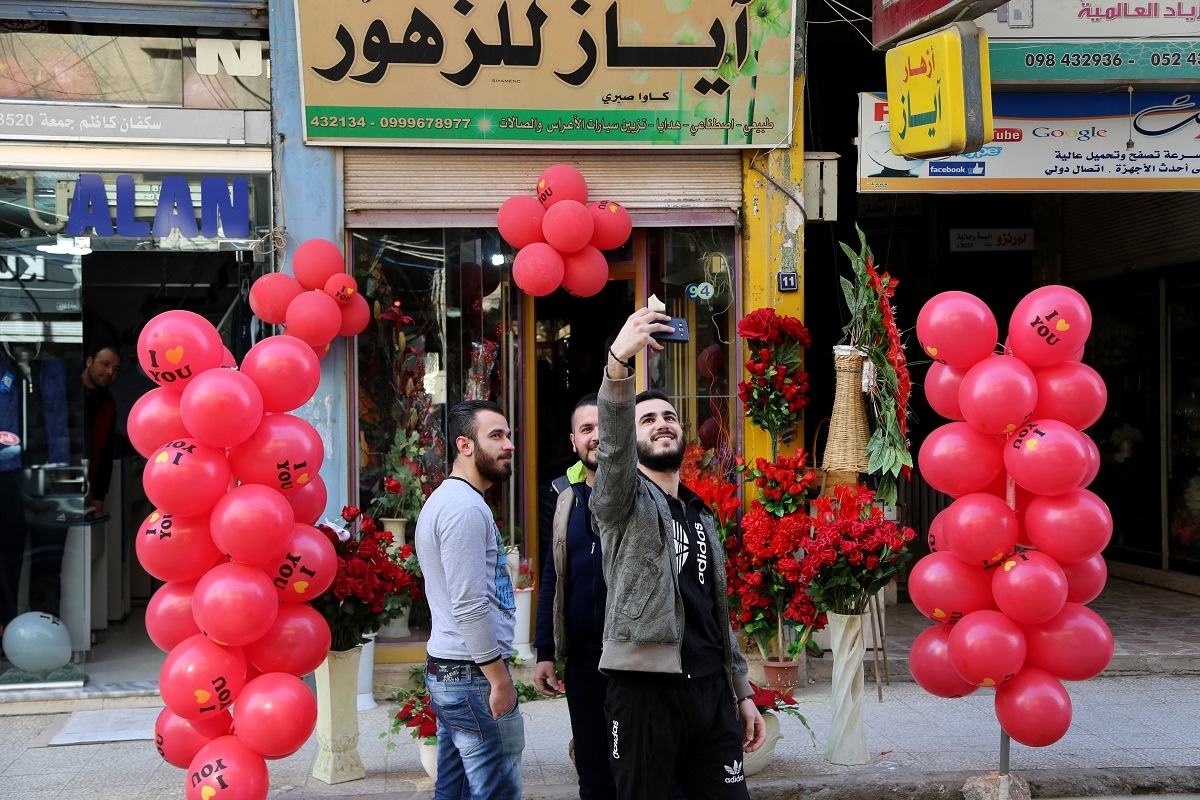 Syrian men take a selfie in front of a shop displaying Valentine's day gifts in the northeastern city of Qamishli on February 13, 2016.