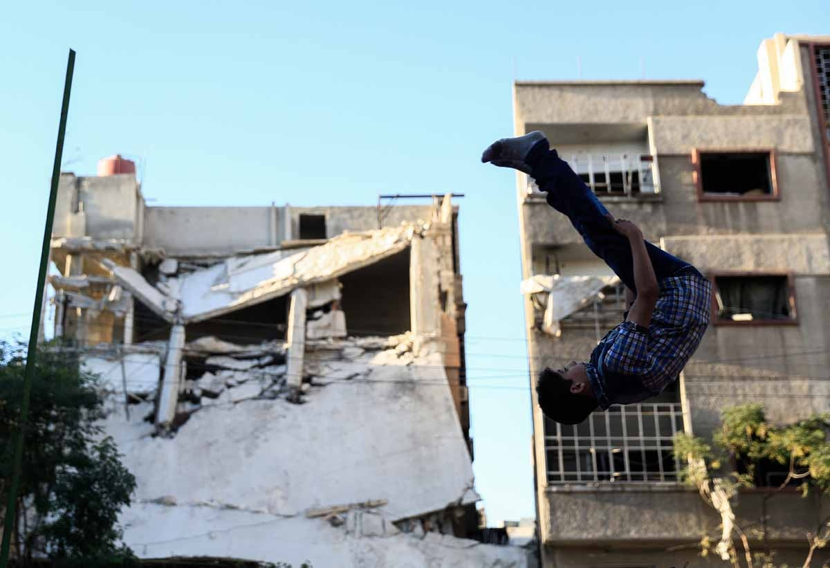 A Syrian boy jumps as he plays in the rebel-held town of Douma, on the eastern edges of the capital Damascus, on the second day of Eid al-Adha Muslim holiday on September 13, 2016.