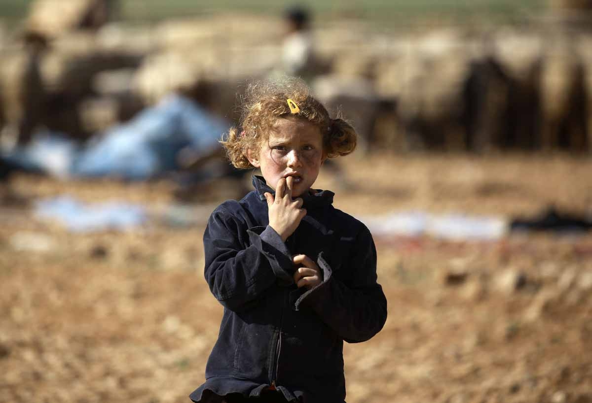 A Syrian child stands at a makeshift camp for displaced people near the town of Manbij on March 6, 2017.