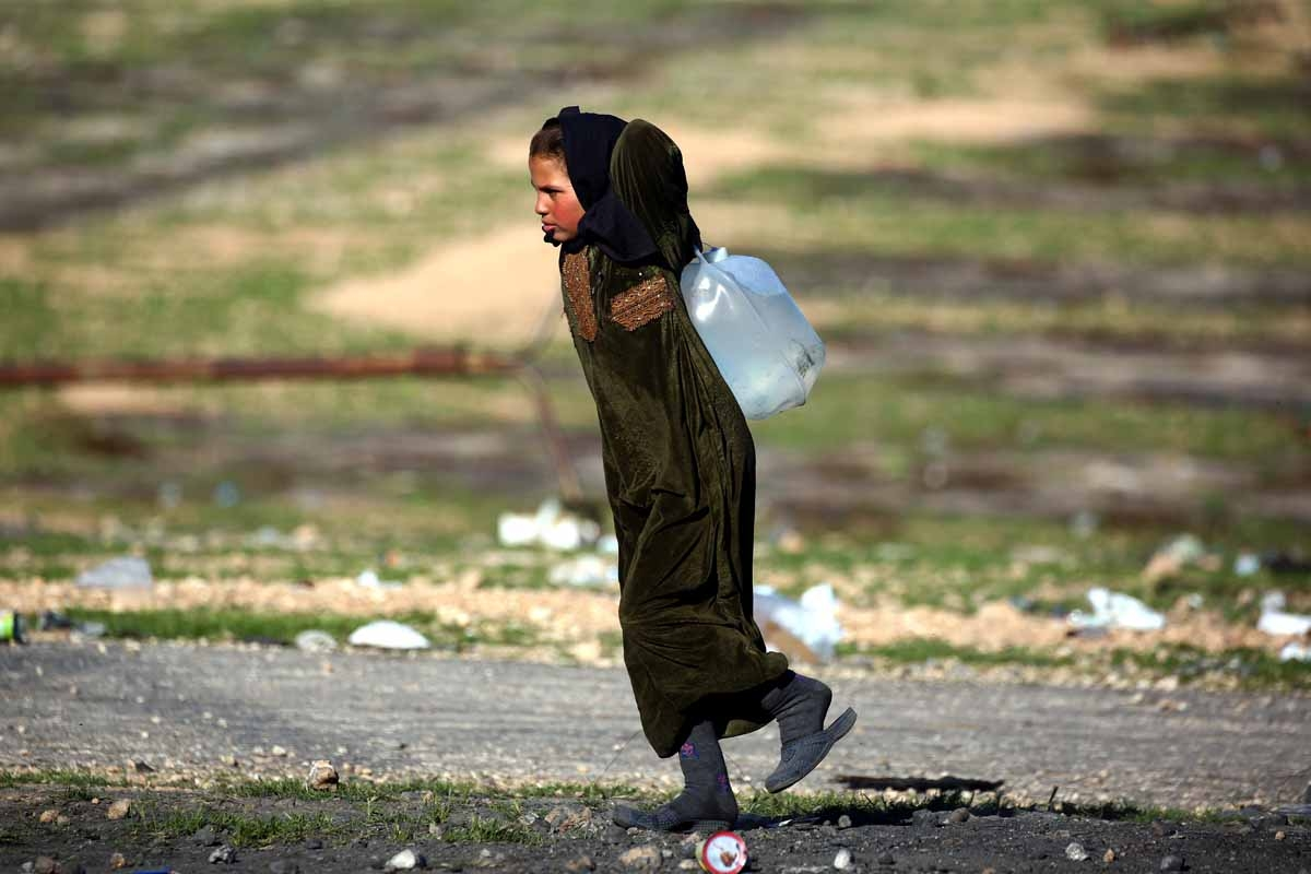 A Syrian girl carries a jug of water at a temporary refugee camp in the village of Ain Issa, housing people who fled Islamic State group's Syrian stronghold Raqa, some 50 kilometres (30 miles) north of the group's de facto capital on March 25, 2017.