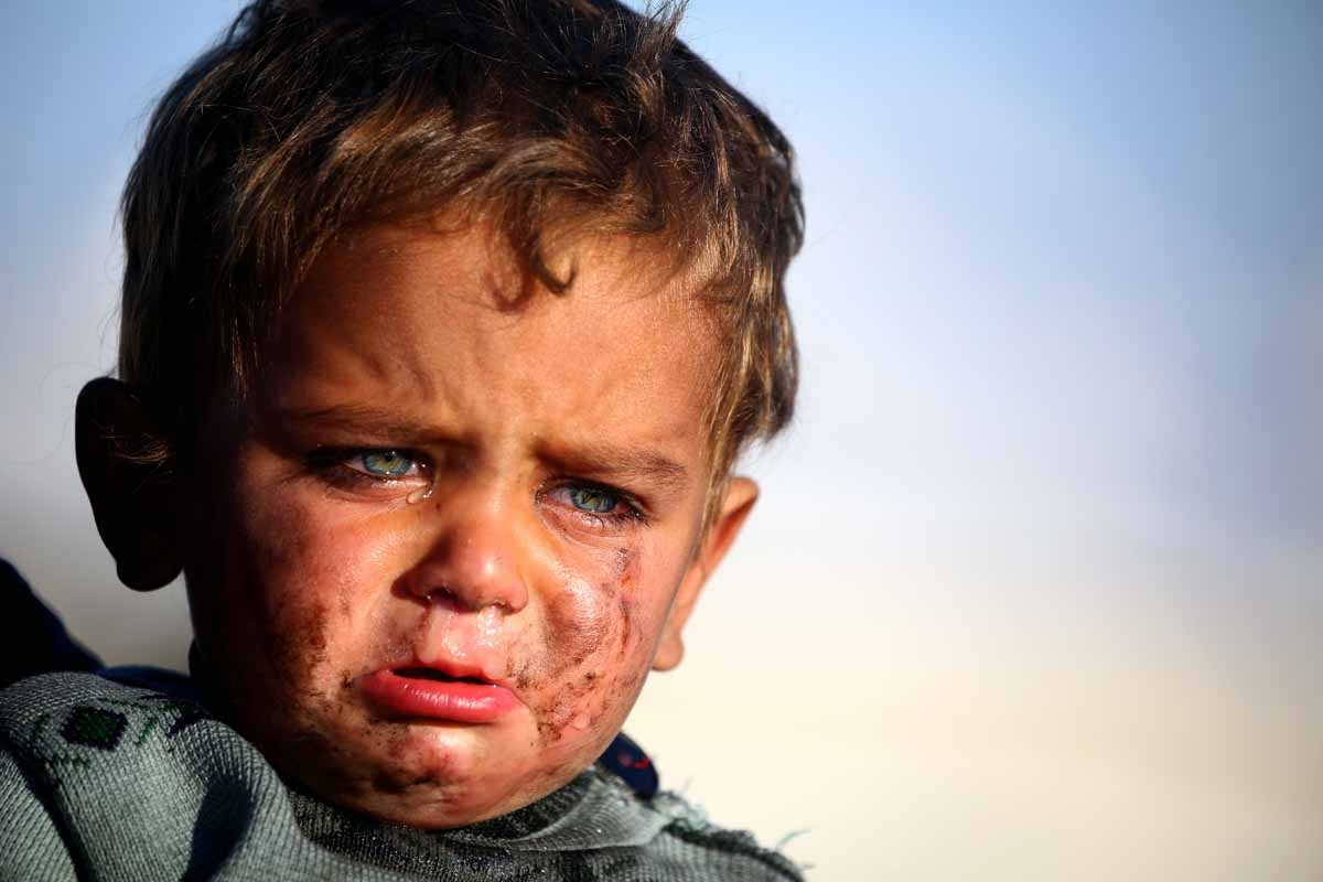 A Syrian boy cries as he is being held at a temporary refugee camp in the village of Ain Issa, housing people who fled Islamic State group's Syrian stronghold Raqa, some 50 kilometres (30 miles) north of the group's de facto capital on March 25, 2017.
