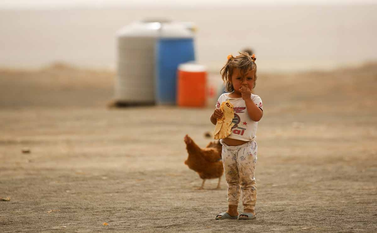 A displaced child, who fled from the Islamic State (IS) group bastion of Raqa, stands outside as she eats a loaf of bread in a camp for displaced near the town of al-Karamah, 26 kms from Raqa, on May 10, 2017.