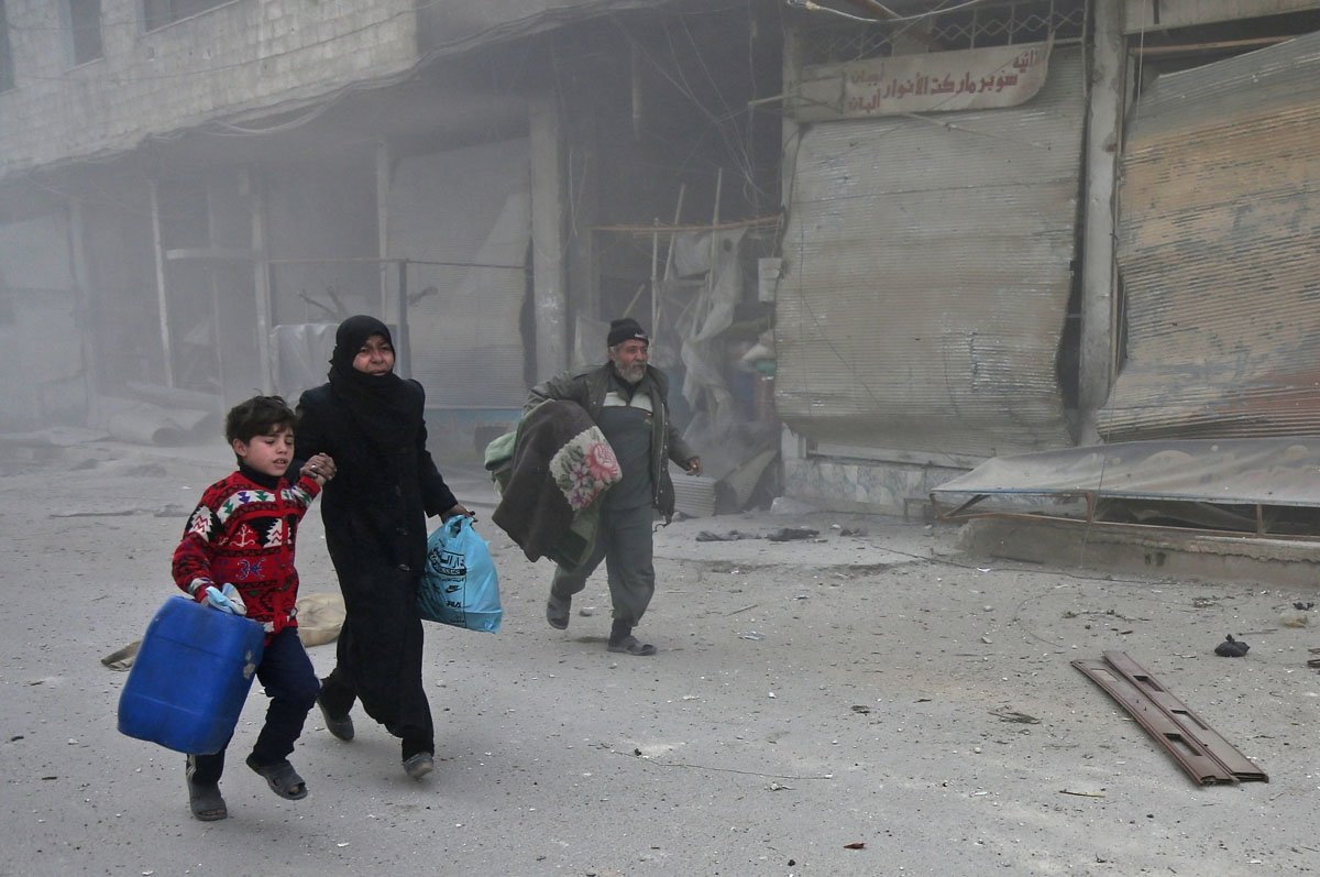 Syrians run for cover in Hamouria during Syrian government shelling on rebel-held areas in the Eastern Ghouta region on the outskirts of the capital Damascus on March 6, 2018. Heavy air strikes and clashes shook the Syrian rebel enclave of Eastern Ghouta,