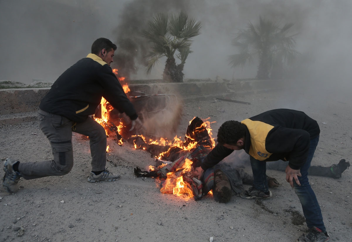 Syrian aid workers try to put out a fire engulfing a man fatally wounded in the bombardment in Hammuriyeh, March 7, 2018.