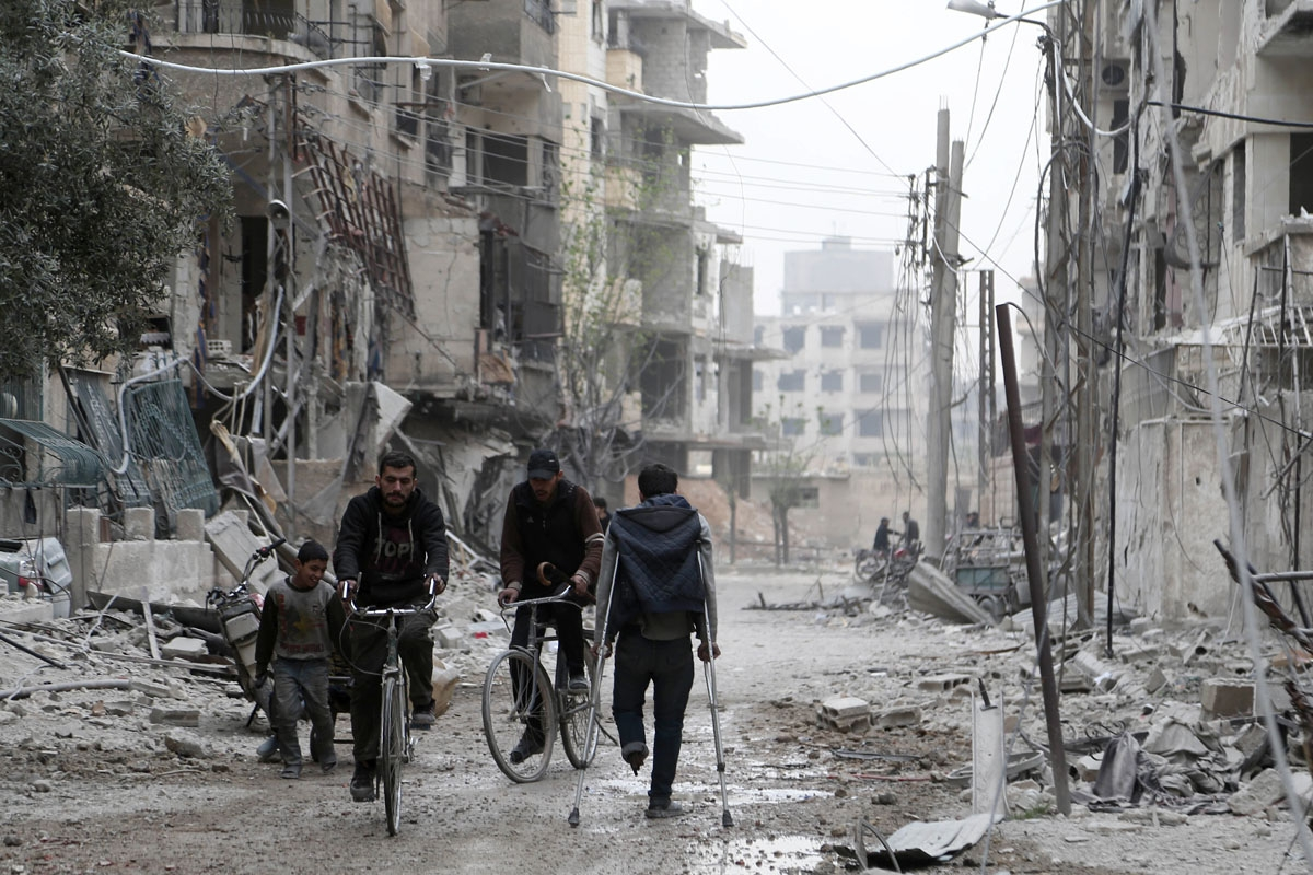Syrian people walk down a destroyed street as civilians and rebels prepare to evacuate one of the few remaining rebel-held pockets in Zamalka, in Eastern Ghouta, on the outskirts of the Syrian capital Damascus, on March 24, 2018. Syrian rebels and civilia