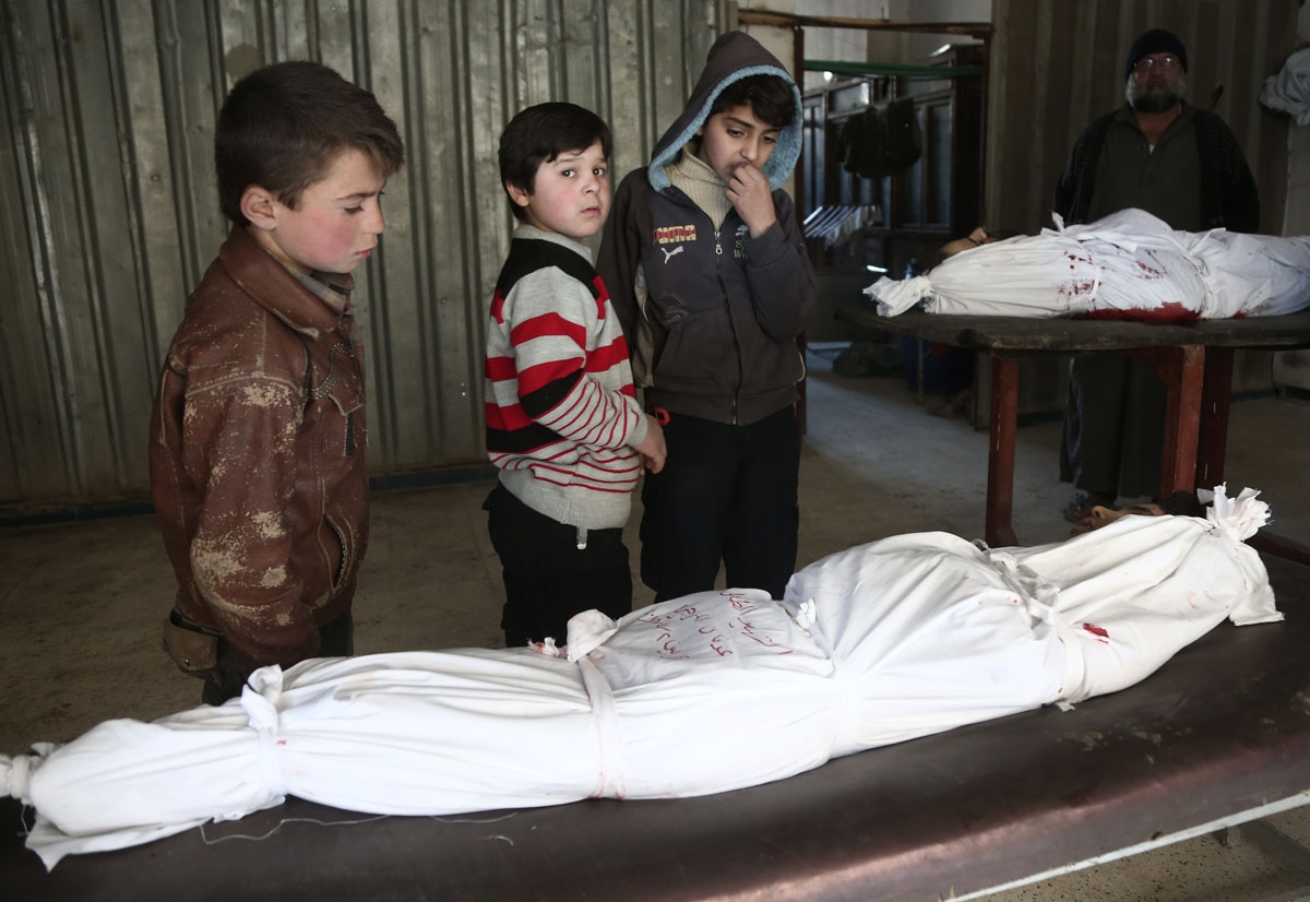 Children stand over the body of a child at a makeshift hospital, following an airstrike in the rebel-held besieged town of Arbin, in the eastern Ghouta region on the outskirts of the capital Damascus on February 2, 2018.
