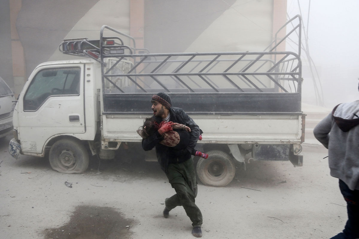 / A man carries a child as he flees from reported Syrian air force strikes that hit the rebel-held town of Saqba, in the besieged Eastern Ghouta region on the outskirts of the capital Damascus, on February 6, 2018.