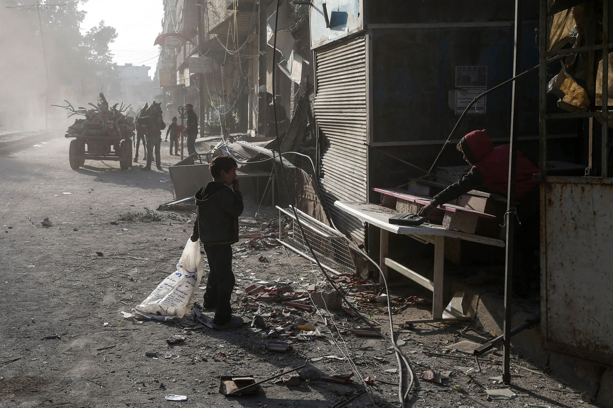 Syrian children clean up their shop from debris following reported regime air strikes in the rebel-held town of Kafr Batna, in the besieged Eastern Ghouta region on the outskirts of the capital Damascus, on February 6, 2018.