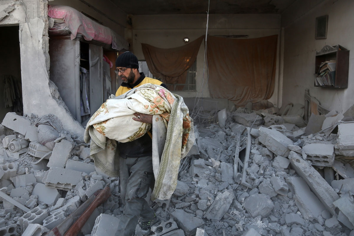 A member of the Syrian civil defence carries the body of a child out of the rubble of a house that was hit by a reported regime air strike in the rebel-held town of Jisreen, in the besieged Eastern Ghouta region on the outskirts of the capital Damascus, o