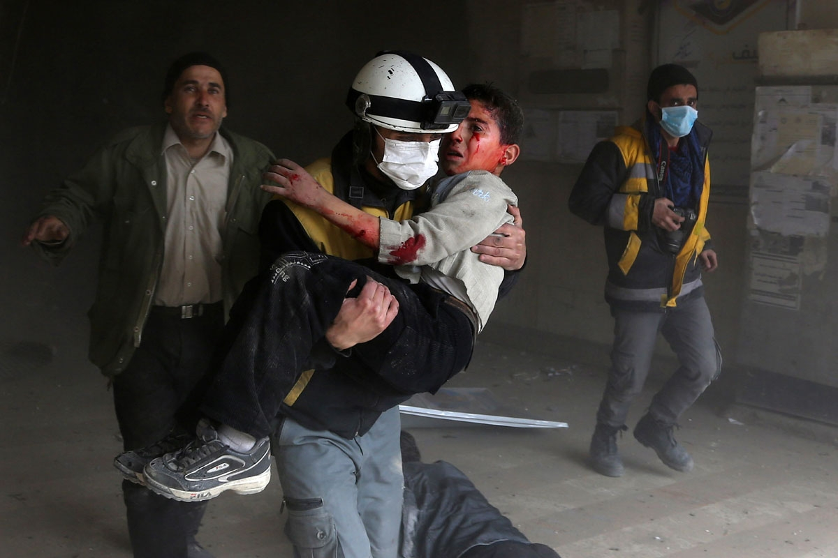 A member of the Syrian civil defence carries a wounded child from the rubble after a reported regime air strike in the rebel-held town of Jisreen, in the besieged Eastern Ghouta region on the outskirts of the capital Damascus, on February 8, 2018.