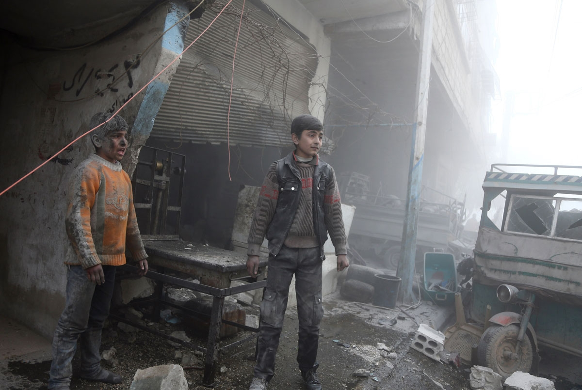 Syrian children covered in dust walk out of a shop following reported Syrian air force strikes in the rebel-held town of Saqba, in the besieged Eastern Ghouta region on the outskirts of the capital Damascus on February 8, 2018.