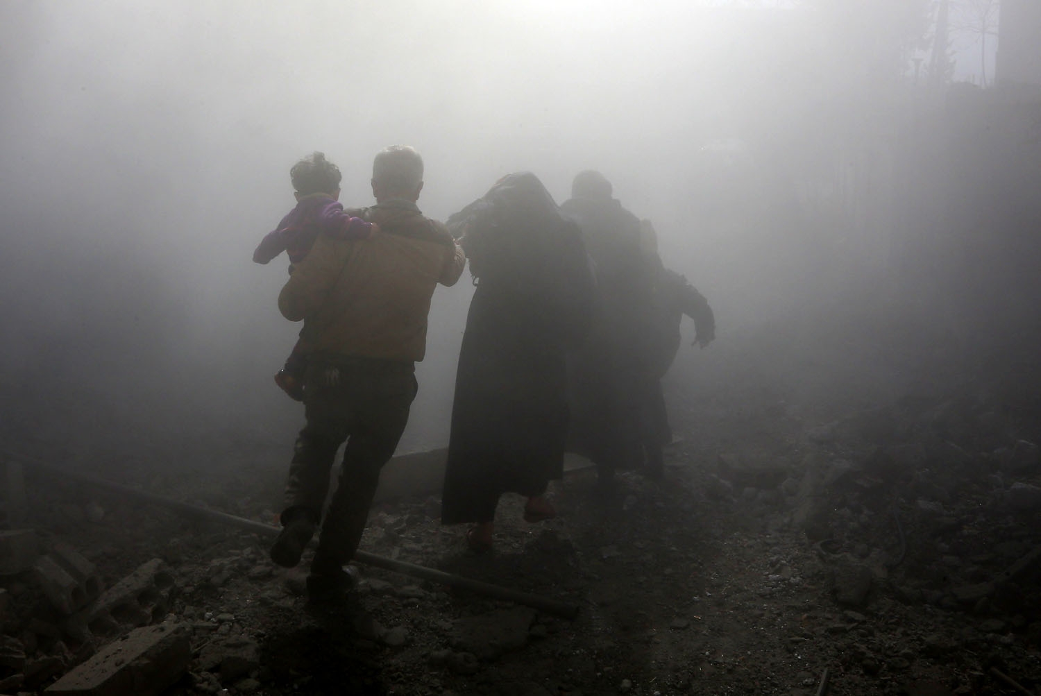 A Syrian family walks through a dust cloud while fleeing from reported regime air strikes in the rebel-held town of Jisreen, in the besieged Eastern Ghouta region on the outskirts of the capital Damascus, on February 8, 2018.