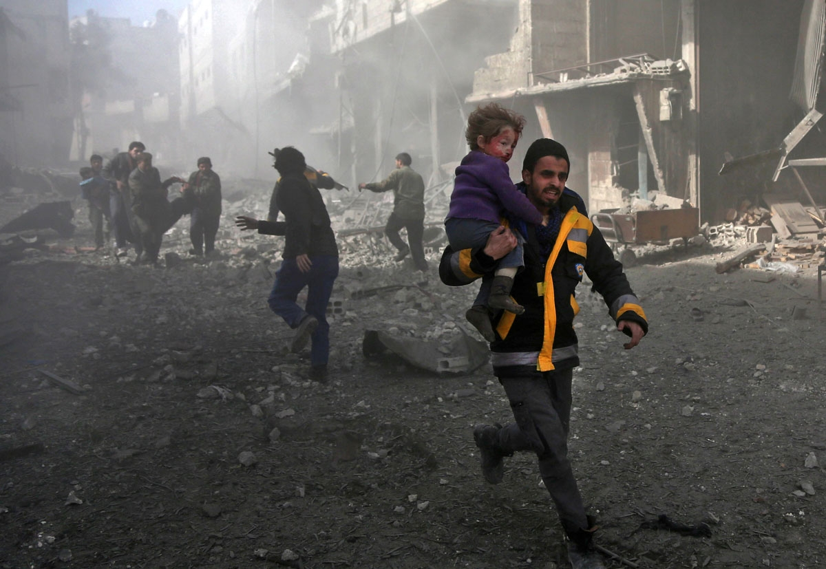 A Syrian man carries an infant rescued from the rubble of buildings following government bombing in the rebel-held town of Hamouria, in the besieged Eastern Ghouta region on the outskirts of the capital Damascus, on February 19, 2018.