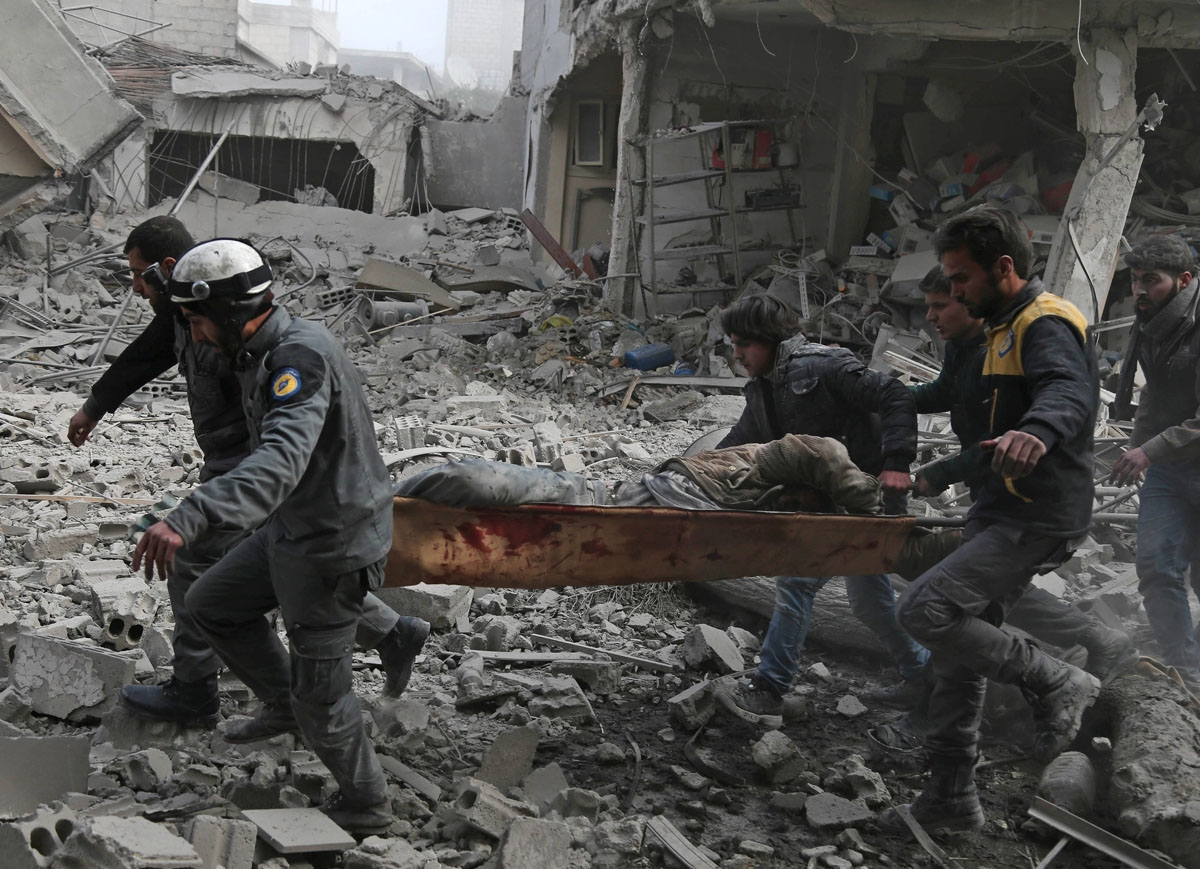 Members of the Syrian civil defence evacuate an injured civilian on a stretcher from an area hit by a reported regime air strike in the rebel-held town of Saqba, in the besieged Eastern Ghouta region on the outskirts of the capital Damascus, on February 2