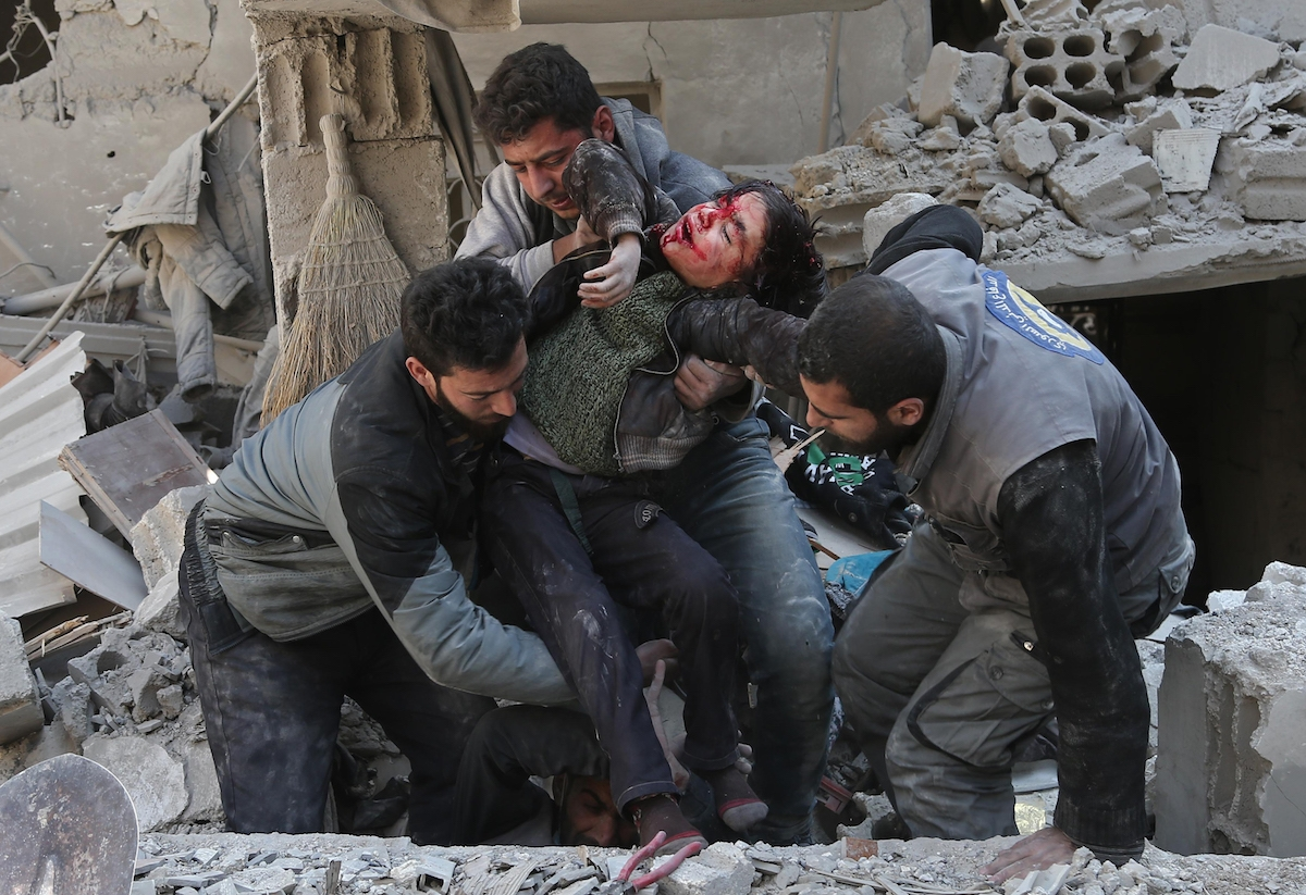 EDITORS NOTE: Graphic content / Syrians rescue a child following a reported regime air strike in the rebel-held town of Hamouria, in the besieged Eastern Ghouta region on the outskirts of the capital Damascus on February 21, 2018.