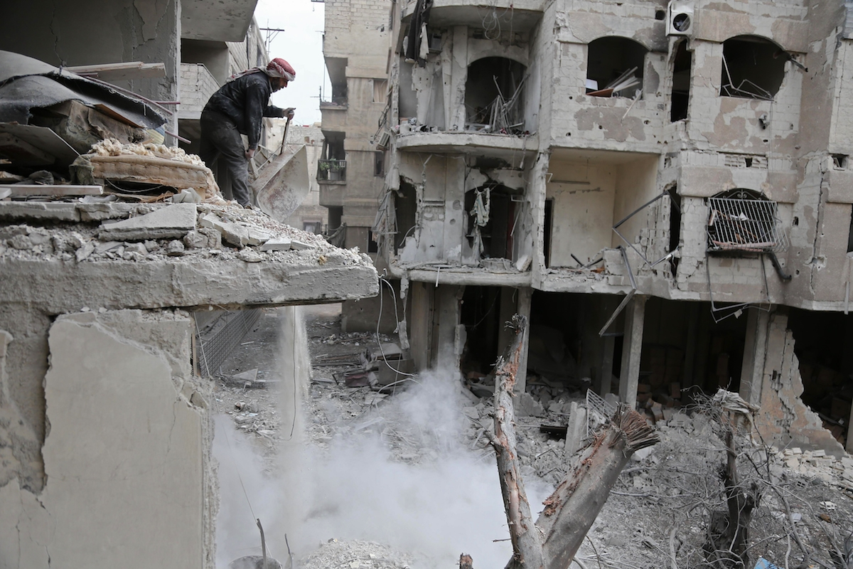 A Syrian man checks the site of Syrian government bombardments in Hamouria, in the  besieged Eastern Ghouta region on the outskirts of the capital Damascus on February 22, 2018.