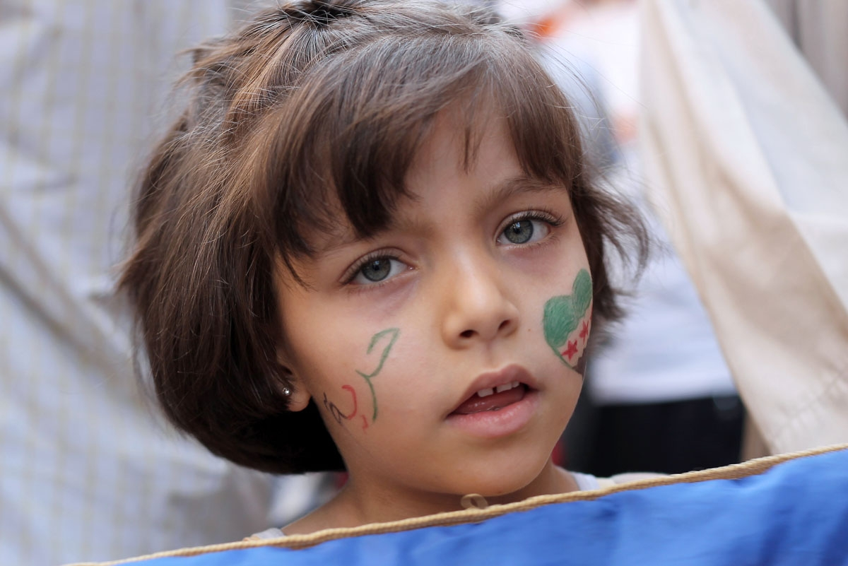 A girl with the colours of the Syrian revolutionary flag painted on her cheek takes part in an anti-government demonstration in the Bustan al-Qasr neighbourhood of northern Syrian city of Aleppo on October 4, 2013.